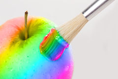 Rainbow apple close-up with water drops being painted on a white Stock Image