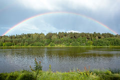 Rainbow arc over trees. By the lake Stock Image