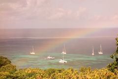 A rainbow arched over yachts at bequia Stock Photography