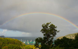 A rainbow arching over a bay in the caribbean Stock Photography