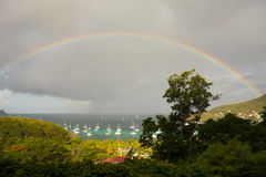 A rainbow arching over a bay in the caribbean Stock Image