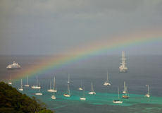 A rainbow arching over a bay in the caribbean Royalty Free Stock Photos