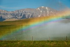 Rainbow around the farmers water sprayer machine, Alberta, Canada. Farming, water magic royalty free stock photography