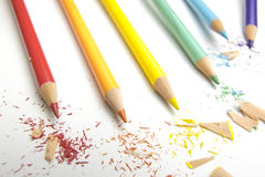 Rainbow arts pencils with shavings on white. Rainbow colored drawing pencils with shavings on white paper Stock Photo