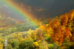 Rainbow and Autumn. Bright rainbow and the autumn forest on a hillside stock photo