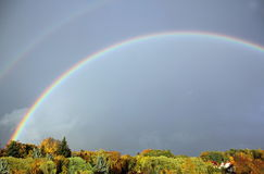 Rainbow in autumn. A double rainbow stretches over a park landscape in autumn. The leaves are colored  in autumn colors and it seems as if the rainbow sheds its Royalty Free Stock Images