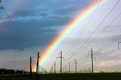 Rainbow. On a background of a dark gray spring sky and a green field Royalty Free Stock Photography