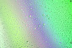 Rainbow background with many tiny drops. Cold rainbow background with many tiny and some big drops. there are shades of green and blue Royalty Free Stock Image