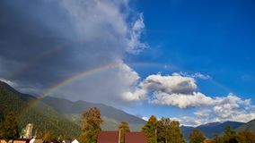 Rainbow on a background of mountains, blue sky, clouds royalty free stock image