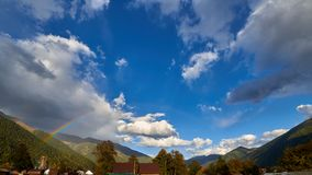 Rainbow on a background of mountains, sky and clouds stock photo