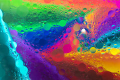 Rainbow background with oil spot bubbles on water surface Stock Photos