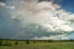 Rainbow on a background of rain above the fields and thunderclouds Royalty Free Stock Photo
