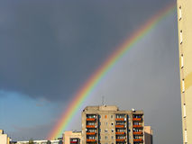 Rainbow. On the background of sunlit housing blocks and a cloudy gray sky Royalty Free Stock Images