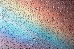 Rainbow background with tiny drops. Colorful rainbow background with tiny and some big drops with a cheerful mood Stock Image