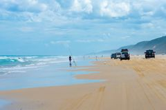 4wd vehicles at Rainbow Beach with coloured sand dunes, QLD, Australia. Rainbow Beach, QLD, Australia- December 30, 2017: 4wd vehicles at Rainbow Beach, a royalty free stock image