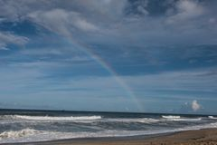 Rainbow on Beach with Stormy Blue Skies royalty free stock images