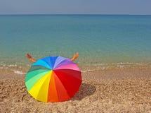 Rainbow beach umbrella and sea Royalty Free Stock Images
