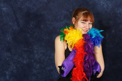 Rainbow Beauty. Beautiful red-head in bright rainbow colored boa Stock Photo