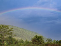 The rainbow behind mountain. In sunny day royalty free stock photography