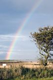 Rainbow with blank sign at the end. A rainbow over the countryside in Fife, Scotland. The text on the sign has been removed for customized use of the blank space Stock Photography
