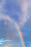 Rainbow in blue cloudy sky Stock Images