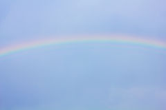 Rainbow in the blue sky as background Stock Image