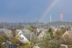 Rainbow in the blue sky as background. Beautiful classic rainbow across in the blue sky after the rain over the suburb and the plant's tower Stock Photography