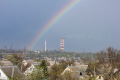 Rainbow in the blue sky as background. Beautiful classic rainbow across in the blue sky after the rain over the suburb and the plant's tower Royalty Free Stock Photo