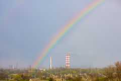 Rainbow in the blue sky as background. Beautiful classic rainbow across in the blue sky after the rain over the suburb and the plant's tower stock photos