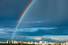 Rainbow in the blue sky after a thunderstorm over the city. Beautiful natural landscape Stock Photo