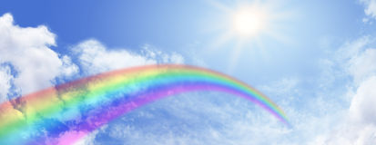 Rainbow and blue sky website banner. Wide blue sky and fluffy clouds background with a rainbow arcing across and bright sunburst Royalty Free Stock Photo