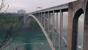 The Rainbow Bridge Connecting Canada and the United States of America. The Niagara River flows slowly underneath. Long shot stock video footage