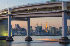 Rainbow bridge at night with Tokyo tower in background Stock Photos
