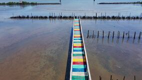 Rainbow bridge in Thailand.View of The colorful wood bridge extends into the sea under blue sky at samut sakhon province,Thailand stock video footage