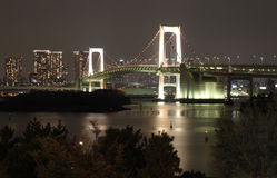 Rainbow Bridge Tokyo at Night. With trees in the foreground, time motion blurred water in the middle and Cityscape background stock images