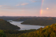 Rainbow at Broken Bow Lake. A rainbow in the sky during a beautiful sunset at Broken Bow Lake, Oklahoma Royalty Free Stock Image