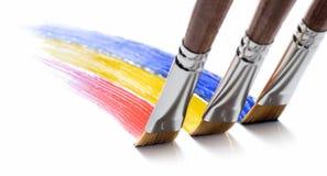Rainbow brushes. Three brushes painting a rainbow Stock Photos
