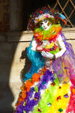 A Rainbow Butterfly Masquerader. A lady dressed in a colorful rainbow butterfly costume at Venice's Carnival in Saint Mark's Square stock image