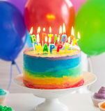 Rainbow cake and cupcakes decorated with birthday candles Royalty Free Stock Images