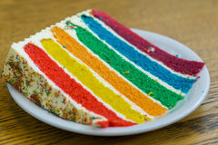 Rainbow cake. With red, yellow, orange, green, blue, purple sponge seperated with fresh cream topped with rainbow mixture, colored sugar stock photo