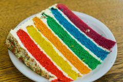 Rainbow cake. With red, yellow, orange, green, blue, purple sponge seperated with fresh cream topped with rainbow mixture, colored sugar stock photography