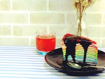 Rainbow cake slice with chocolate sauce. With fruit juice Stock Photography