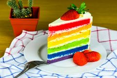 Rainbow Cake and strawberries on the white plate royalty free stock photo