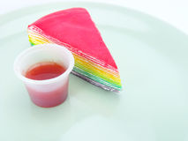 Rainbow cake and strawberry souce on white background Stock Image