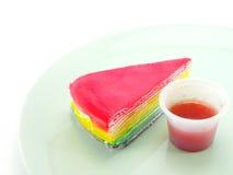 Rainbow cake and strawberry souce on white background. Rainbow layer cake and strawberry souce on white background Stock Photos