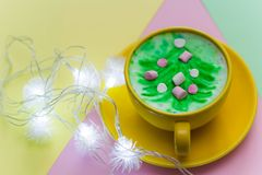 Rainbow cappuccino in a bright yellow mug. Cappuccino with painted christmas tree in a bright yellow mug on bright yellow,pink and green background Royalty Free Stock Photography