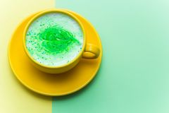 Rainbow cappuccino in a bright yellow mug. On bright yellow and green background Stock Photos
