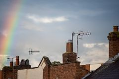 Rainbow over rooftops with storm clouds in background stock photos