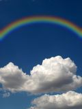 Rainbow and cloud. Rainbow and white fluffy cloud on a background of the dark blue sky royalty free stock photos