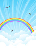 Rainbow and clouds. Rainbow in the clouds. Blue sky lit by the sun. Swallows fly in the sky Royalty Free Stock Images